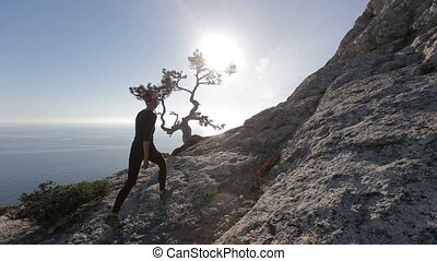 Young woman walking high in mountains above a sea. Lady on the summit in beautiful scenery observing Black sea from a hight in Crimea.