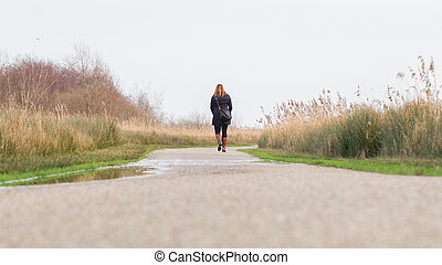 Young woman walking in a dutch landscape
