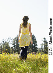Young woman walking in a field of wildflowers (rear view)