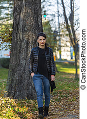 Young Woman Walking in a Park in Autumn
