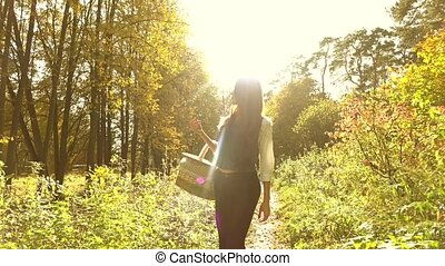 Young woman walking in autumn forest holding a picnic basket. Slow motion steadicam clip