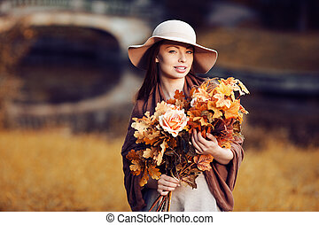 Young woman walking in autumn park with a bouquet of fall...