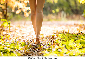 Young woman walking in forest barefoot