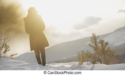 Young woman walking in frosty wintertime forest, natural landscape