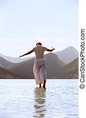 Young woman walking in lake