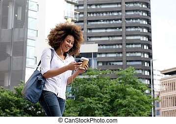 Young woman walking in the city with cellphone