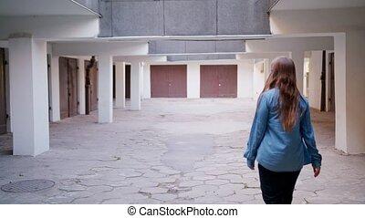Young Woman Walking in the Courtyard - A young woman walking...