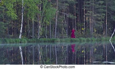 Young woman walking in the forest near the lake