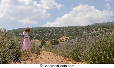 Young woman walking in the lavanda field