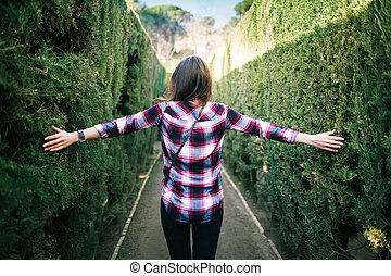 Young woman walking in the park labyrinth in Barcelona