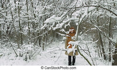 Young Woman Walking in Winter Forest