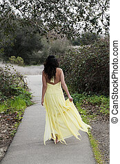 Young Woman Walking in Yellow Dress Outdoors