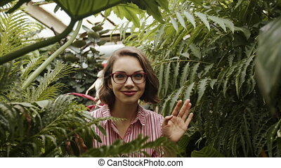 Beautiful young woman walking in botanical garden, looking at camera. Slow motion.
