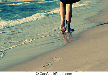 young woman walking on a beach