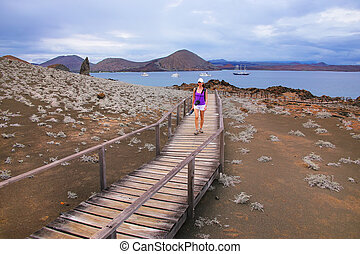 Young woman walking on a boardwalk on Bartolome island, Galapagos National Park, Ecuador.
