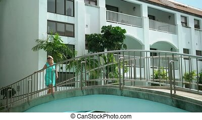 Young woman walking on a bridge in resort