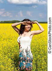 Young woman walking on a field of yellow flowers