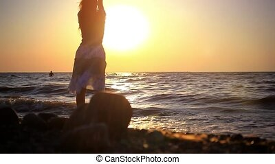 Young woman walking on a rocky beach at sunset, splashes...