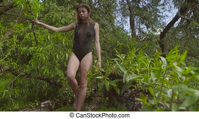 Young woman walking on a tree branch. - Young woman in a...