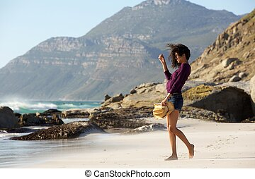 Young woman walking on beach in shorts