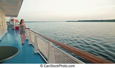 Young woman walking on deck of cruise ship
