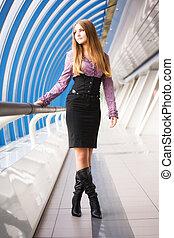 Young woman walking on modern bridge. Soft colors.