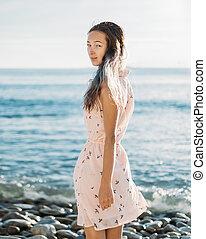 Young woman walking on pebble beach