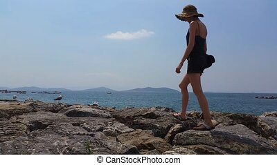 Young Woman walking on rocks near the sea