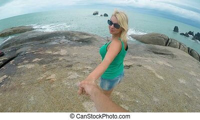 Young woman walking on rocky beach holding man hand