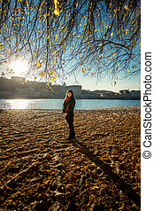 woman walking on sandy beach at cold autumn day