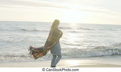 Young woman walking on shore of the sea. Pensive female with plaid spending time alone on the beach in windy cold day.