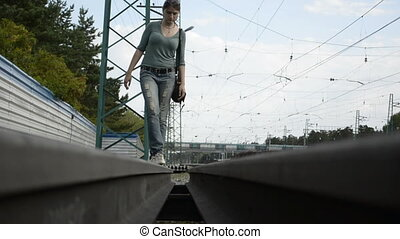 Young woman walking on the rail