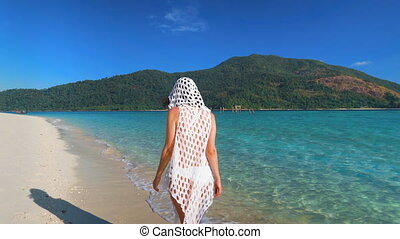 Young woman walking on tropical beach in paradise island. ...