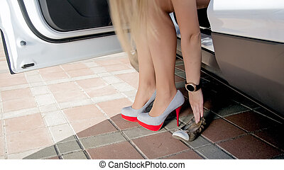 Young woman walking out of the car and changing comfortoble shoes to high heels