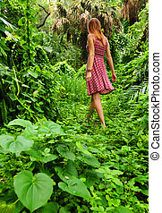 Young woman walking through forest