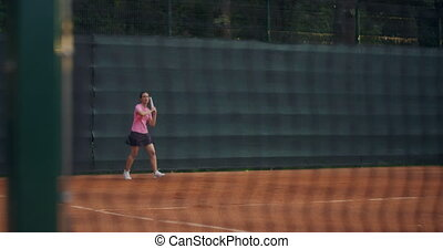 Young woman walking through tennis court with racket. ...