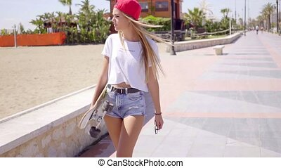 Young woman in white shirt and blue jeans shorts holding skateboard in her arms while looking toward sand