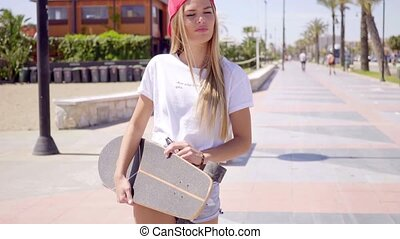 Young woman walking while holding skateboard