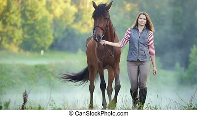 Young woman walking with a horse in nature, close up