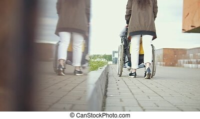 Young woman walking with disabled man in a wheelchair down the street