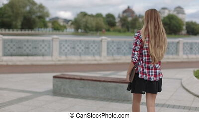 Young woman walking with laptop in city park passes by camera