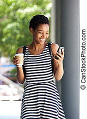 young woman walking with mobile phone and coffee cup in the city