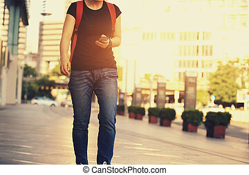 young woman walking with smart phone in modern city