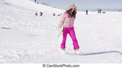 Young woman walking with snowboard - Young woman in pink...