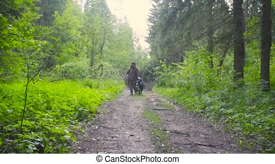 Young woman walking with the dog in the forest