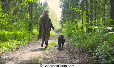 Young woman walking with the dog in the forest - Young woman...