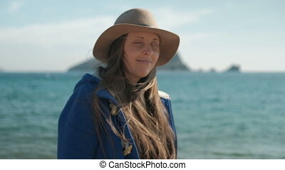 Young woman walks along beach in hat and looks at camera and around.