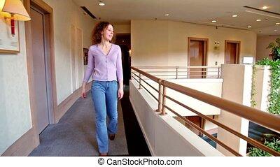 Young woman walks along corridor in multiple floor building