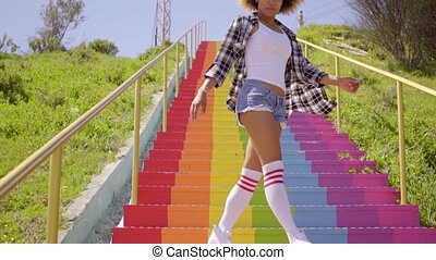 Young Woman Walks Down The Colorful Stairs.