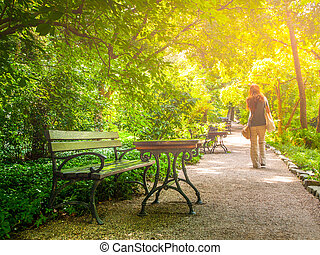 Young woman walks in the park on sunny summer day